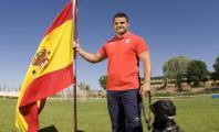 David Casinos portando la bandera española y acompañado de un perro guía