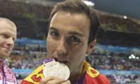 Enrique Floriano mordiendo su medalla de plata
